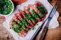 Bife grelhado cortado do assado com molho verde do chimichurri foto de stock royalty free