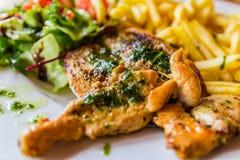 Bife grelhado da galinha seved com vegetais e microplaquetas de batata foto de stock royalty free