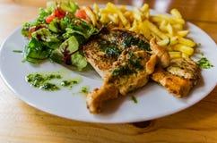Bife grelhado da galinha seved com vegetais e microplaquetas de batata na tabela de madeira imagem de stock royalty free