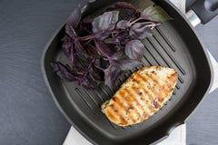 Bife grelhado do peito de frango com manjericão violeta no gri da bandeja do Teflon imagens de stock