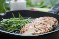 Bife grelhado do peito de frango com rúcula na grade da bandeja do Teflon imagens de stock royalty free