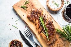 Bife grelhado do striploin da carne com vidro de vinho tinto imagens de stock royalty free