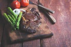 Bife grelhado em um fundo rústico de madeira fotografia de stock royalty free
