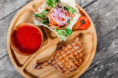 Bife grelhado no osso, na salada fresca, em vegetais grelhados e em molho de tomate na placa de corte no fundo de madeira Foto de Stock Royalty Free