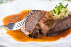 Bife grelhado raro cortado Ribeye com molho na placa branca Foco seletivo imagem de stock royalty free