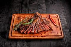 Bife grelhado raro médio cortado na placa de corte rústica com alecrins e especiarias, fundo de madeira rústico escuro, parte sup imagem de stock royalty free