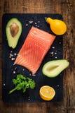 Bife Salmon, abacates, limões, salsa e especiarias na placa de corte de madeira Foto de Stock