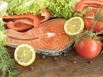 Bife salmon cru em uma placa de madeira cercada por vegetais e por especiarias Foto de Stock Royalty Free