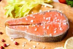 Bife salmon cru fresco na placa de corte com sal e pimenta cor-de-rosa Foto de Stock