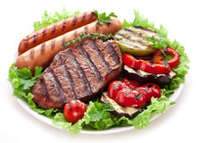 Bife, salsichas e vegetais grelhados. imagens de stock