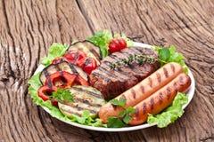 Bife, salsichas e vegetais grelhados. imagem de stock