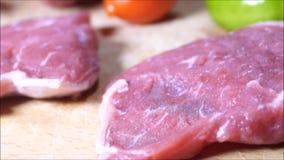 Bifes, carne à terra na placa de corte e parte superior contrária video estoque