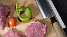 Bifes, carne à terra na placa de corte e parte superior contrária vídeos de arquivo