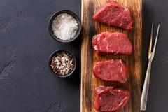 Bifes crus do mignon de faixa da carne com as especiarias na placa de madeira no fundo preto Imagens de Stock