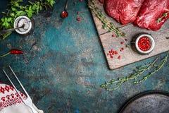 Bifes da carne crua com temperos frescos no fundo de madeira rústico, vista superior Imagens de Stock Royalty Free