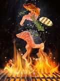 Bifes de salmões saborosos que voam acima da grelha do ferro fundido com chamas do fogo fotos de stock royalty free