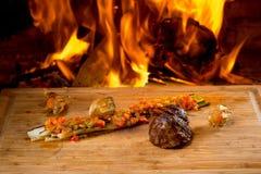Bifes deliciosos na mesa e no fogo de madeira fotografia de stock