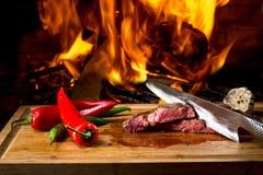 Bifes deliciosos na mesa e no fogo de madeira imagens de stock