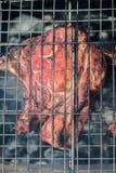 Bifes e grade da carne de porco no fogo ardente Imagem de Stock