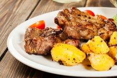 Bifes grelhados, batatas cozidas e vegetais Fotos de Stock