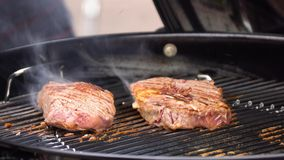 Bifes na grade com chamas Cozinhando bifes nos carvões Conceito de comer a carne foto de stock