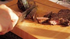Bifes que estão sendo cortados em uma placa de corte de madeira
