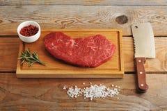 Biff av marmorerat nötkött på brädet med rosmarin, kryddor och A M. Arkivfoto