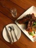 Biff för grisköttstöd med saftig grillfestsås och sallad i plattan som är klar att äta med exponeringsglas av vatten på trätabell royaltyfria foton