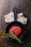 Biff för rått kött på gjutjärnstekpannan Royaltyfri Foto