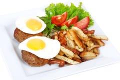 Biff med ägget, småfiskar, tomat, grönsallat Royaltyfria Foton