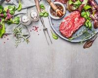 Biff och grön sallad Köttförberedelsen och att marinera för galler eller BBQ på grå färger stenar bakgrund arkivfoton