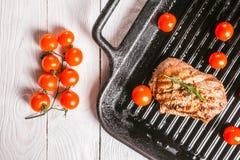 Biff och körsbärsröda tomater i en panna Fotografering för Bildbyråer
