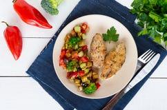 Biffar av den stekte kryddiga fisken som tjänas som med en varm grönsaksallad på en keramisk platta Royaltyfria Bilder