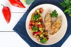 Biffar av den stekte kryddiga fisken som tjänas som med en varm grönsaksallad på en keramisk platta Arkivfoto