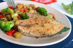 Biffar av den stekte kryddiga fisken som tjänas som med en varm grönsaksallad på en keramisk platta Royaltyfri Fotografi