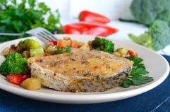 Biffar av den stekte kryddiga fisken som tjänas som med en varm grönsaksallad på en keramisk platta Royaltyfri Foto
