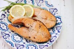Biffar grillar den röda fisken med citronen Fotografering för Bildbyråer