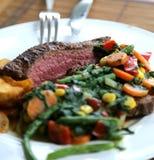 Biffplatta för lunch med grönsaker som sidomaträtt fotografering för bildbyråer