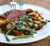 Biffplatta för lunch med grönsaker som sidomaträtt arkivfoton