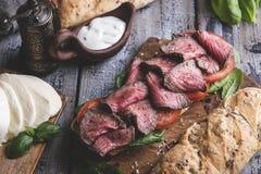 Biffsmörgås, skivat steknötkött Hem bakat bröd, mozzarellaost, spenatsidor, tomat fotografering för bildbyråer