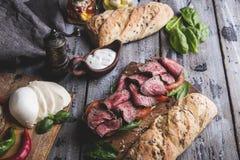 Biffsmörgås, skivat steknötkött, ost, spenatsidor, tomat royaltyfria bilder