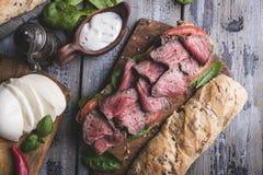 Biffsmörgås, skivat steknötkött, ost, spenatsidor, tomat arkivfoto