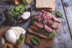 Biffsmörgås, skivat steknötkött, ost, spenatsidor, tomat Lantligt på en träyttersida royaltyfria bilder