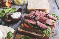 Biffsmörgås, skivat steknötkött, ost, spenatsidor, tomat, vit sås royaltyfria bilder