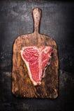 Bifteck à l'os cru sur la planche à découper en bois âgée sur le fond foncé en métal de rouille, vue supérieure Photos stock