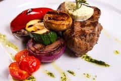 Bifteck épais avec le romarin et le fromage frit de légumes du plat blanc Fin vers le haut Image stock