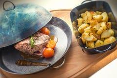 Bifteck avec des tomates et des pommes de terre, casserole en métal, dîner ou nourriture cuit au four de déjeuner, restaurant Photos stock