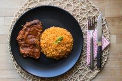 Bifteck avec du riz de sauce tomate et de bulgur dans un plat noir images libres de droits