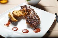 Bifteck avec les pommes de terre grillées avec le côté de salade images libres de droits