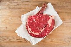 Bifteck avec os de bifteck d'oeil de nervure sur le papier Photos libres de droits